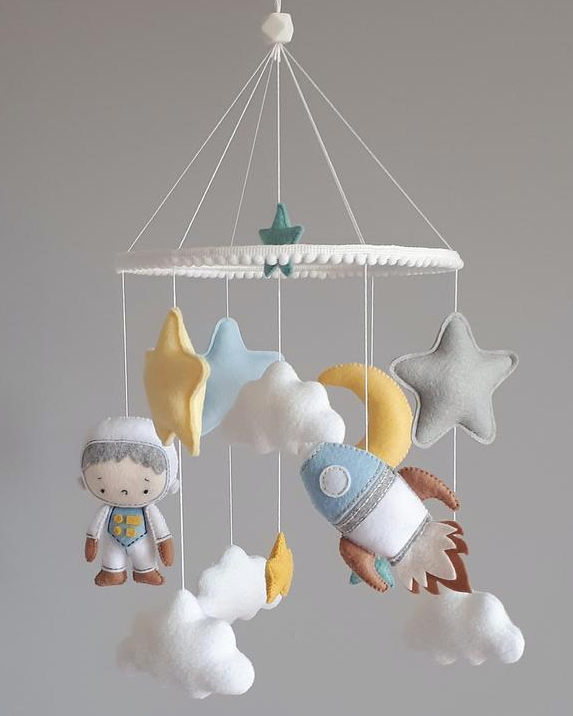 The space mobile in calm colors for boys. The crib mobile with an astronaut and a space rocket